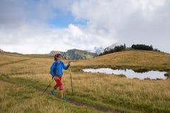 Il nordico di pratica della ragazza sola che cammina con l'escursione attacca in Immagine Stock