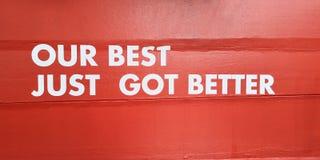 Il nostro migliore appena segno bianco Di tagliato migliorato di parola dell'autoadesivo sulla parete rossa concreta del cemento  fotografie stock libere da diritti