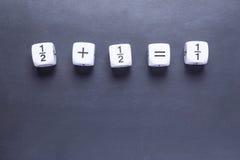 Il numero bianco di mah della frazione taglia la mostra a cubetti dell'equazione semplice sul nero Immagini Stock