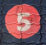 Il numero cinque in un cerchio è sul campo da giuoco del sentiero per pedoni Immagini Stock