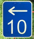 Il numero dieci su un blu di piastra metallica con una freccia bianca che indica a sinistra Fotografia Stock Libera da Diritti
