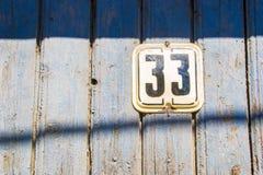 Il numero 33 sul blu di legno ha screpolato la parete fotografia stock