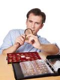 Il numismatico dell'uomo esamina la moneta con la lente d'ingrandimento Immagini Stock