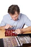 Il numismatico dell'uomo esamina la moneta con una lente d'ingrandimento Immagini Stock Libere da Diritti
