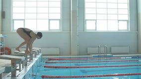 Il nuotatore femminile salta giù il blocchetto cominciare e l'inizio nuota in video del rallentatore dello stagno HD Addestrament video d archivio