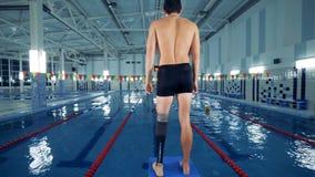Il nuotatore handicappato si scalda vicino ad uno stagno, protesi della gamba archivi video