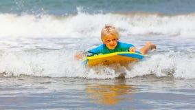 Il nuoto del piccolo bambino con il bodyboard sul mare ondeggia immagine stock