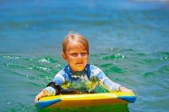 Il nuoto del piccolo bambino con il bodyboard sul mare ondeggia fotografia stock libera da diritti