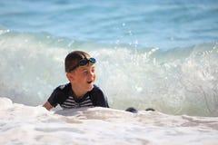 Il nuoto del ragazzo nelle onde del mare Fotografie Stock Libere da Diritti