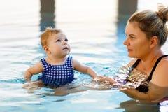 Il nuoto felice della madre con la figlia adorabile sveglia della neonata nella stazione termale di spesa della piscina vacations Immagini Stock