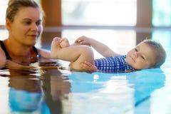 Il nuoto felice della madre con la figlia adorabile sveglia della neonata nella stazione termale di spesa della piscina vacations fotografia stock libera da diritti