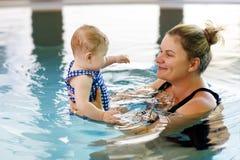 Il nuoto felice della madre con la figlia adorabile sveglia della neonata nella stazione termale di spesa della piscina vacations fotografie stock