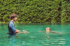 Il nuoto maschio dell'istruttore per i bambini insegna ad un ragazzo felice a nuotare nello stagno fotografia stock