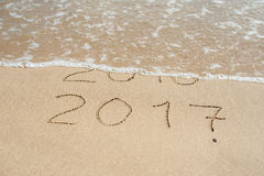 Il nuovo anno 2017 è concetto venente - le iscrizioni 2016 e 2017 su una sabbia della spiaggia, l'onda quasi stanno riguardando l Fotografia Stock Libera da Diritti