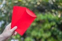 Il nuovo anno cinese felice, mano che tiene la busta rossa o ha chiamato Angpao sul fondo verde del bokeh dagli alberi fotografie stock libere da diritti