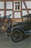Il Oldtimer davanti alla metà ha armato in legno la casa Immagini Stock