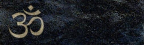 Il OM dorato inciso sul fondo di pietra nero approssimativo dell'insegna Immagine Stock