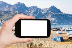 il ourist fotografa la spiaggia di sabbia urbana ed il vecchio porto Immagine Stock Libera da Diritti