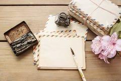 Il pacchetto delle lettere d'annata, della penna e del alstroemeria rosa fiorisce Fotografia Stock