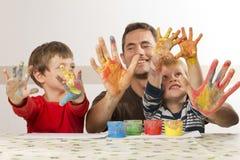 Il padre è pittura con i suoi bambini Immagine Stock