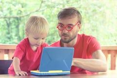 Il padre aiuta suo figlio del bambino ad imparare lavorare ad un computer portatile del giocattolo pres fotografia stock libera da diritti