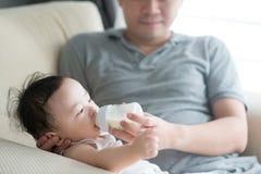 Il padre allatta con il biberon il latte al bambino Fotografia Stock