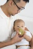 Il padre allatta con il biberon il bambino Fotografia Stock