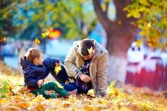 Il padre allegro ed il figlio che si divertono in autunno parcheggiano Fotografia Stock