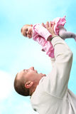 Il padre alza la sua neonata Fotografia Stock