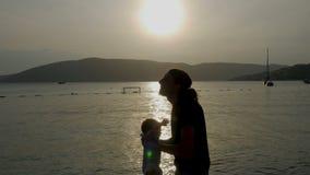 Il padre alza suo figlio al tramonto del mare nel Montenegro stock footage