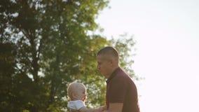 Il padre americano sta girando il primo piccolo bambino, stante nella campagna verde stock footage
