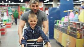Il padre amoroso allegro sta divertendosi in supermercato con il suo piccolo figlio sveglio, lui sta correndo con il carrello con archivi video
