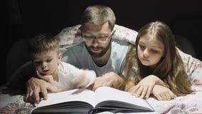 Il padre amoroso legge durante la notte una fiaba per i bambini archivi video