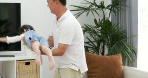 Il padre asiatico felice e piccolo divertiresi della figlia getta sulla ragazza del bambino Nel salone stock footage