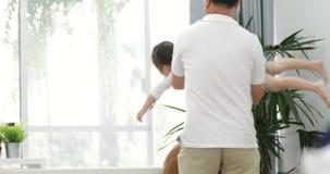 Il padre asiatico felice e piccolo divertiresi della figlia getta sulla ragazza del bambino Nel salone archivi video