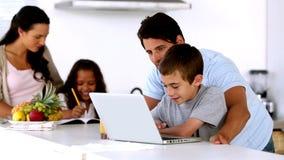 Il padre che esamina il computer portatile con il figlio e la madre entra per aiutare la figlia stock footage