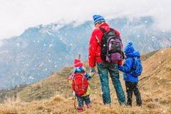 Il padre con due bambini viaggia in montagne sceniche Fotografia Stock
