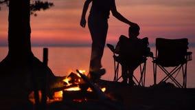 Il padre con il bambino sta sedendo vicino al fuoco di accampamento alla notte archivi video