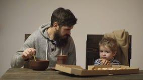 Il padre convince il ragazzo che il porridge sia più delizioso della pizza L'uomo mescola il porridge mentre un ragazzo tiene il  video d archivio