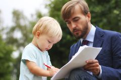 Il padre dà i documenti finanziari a suo figlio, bambino scrive le carte fotografia stock