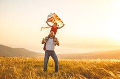 Il padre della famiglia e la figlia felici del bambino funzionano con l'aquilone sul prato Fotografia Stock