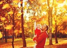 Il padre della famiglia e la figlia felici del bambino su una passeggiata in autunno coprono di foglie Fotografia Stock