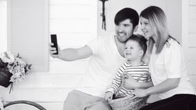 Il padre della famiglia felice fa il selfie con la suoi moglie e piccolo figlio nella parte anteriore la loro porta domestica immagini stock libere da diritti