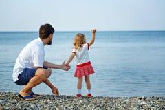 Il padre e la figlia esaminano lontano la spiaggia Fotografia Stock