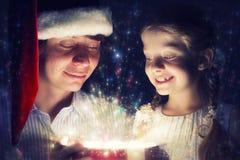 Il padre e la figlia hanno aperto una scatola con un regalo Immagini Stock