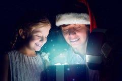 Il padre e la figlia hanno aperto una scatola con un regalo Immagini Stock Libere da Diritti