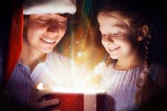 Il padre e la figlia hanno aperto una scatola con un regalo Fotografie Stock