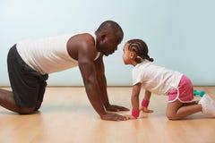Il padre e la sua piccola figlia stanno allungando insieme sul pavimento a casa fotografie stock libere da diritti