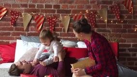 Il padre e madre allegramente gioca con la piccola figlia stock footage