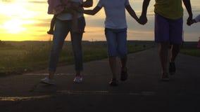 Il padre e madre felice con tre bambini va sulla strada in campagna sul tramonto La famiglia felice si diverte sulla natura Corsa stock footage